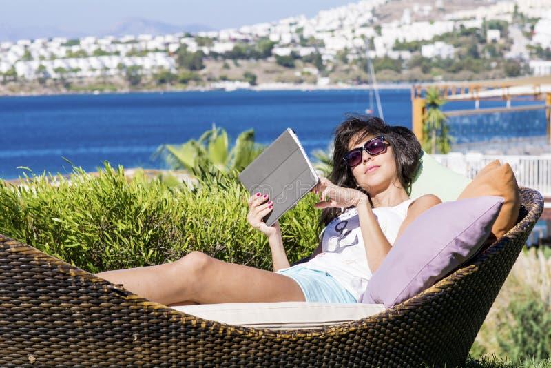 Счастливая женщина наслаждаясь летними каникулами с таблеткой в руках стоковое фото