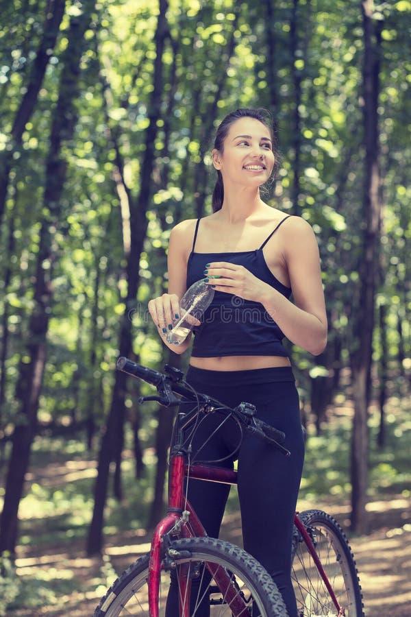 Счастливая женщина на велосипеде стоя на дороге холма наслаждаясь красивым v стоковая фотография