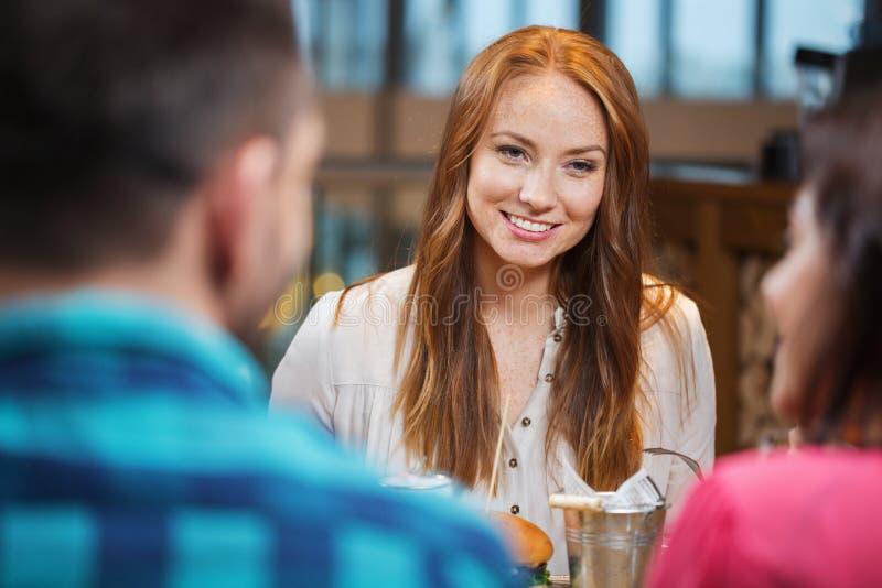 Счастливая женщина обедая с друзьями на ресторане стоковое изображение