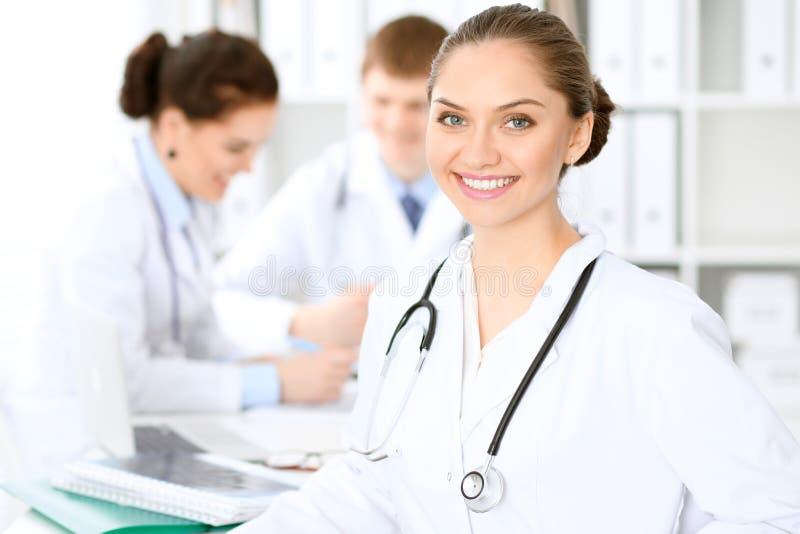 Счастливая женщина доктора с медицинским персоналом на больнице сидя на таблице стоковая фотография