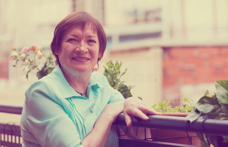 Счастливая женщина пенсионера ослабленная на teracce стоковая фотография rf