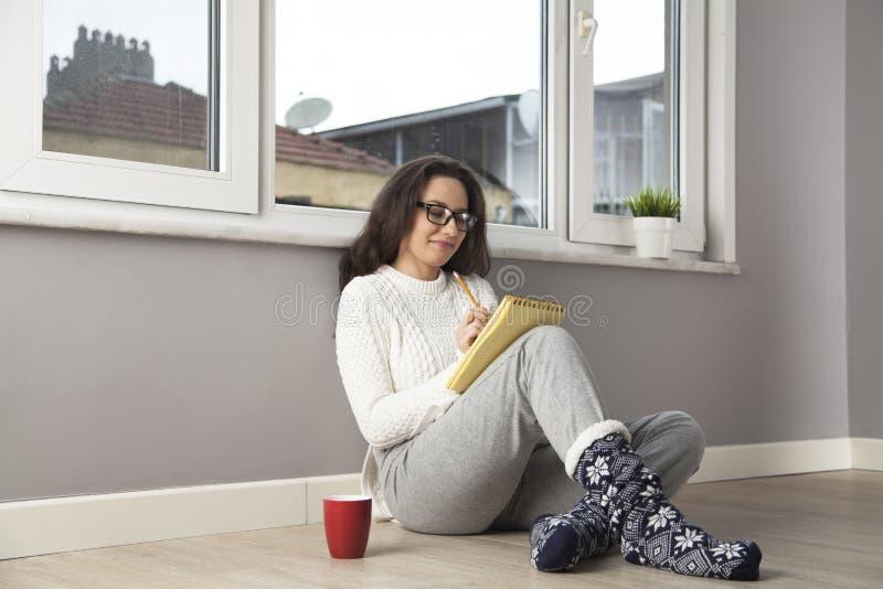 Счастливая женщина писать что-то дома стоковые фотографии rf