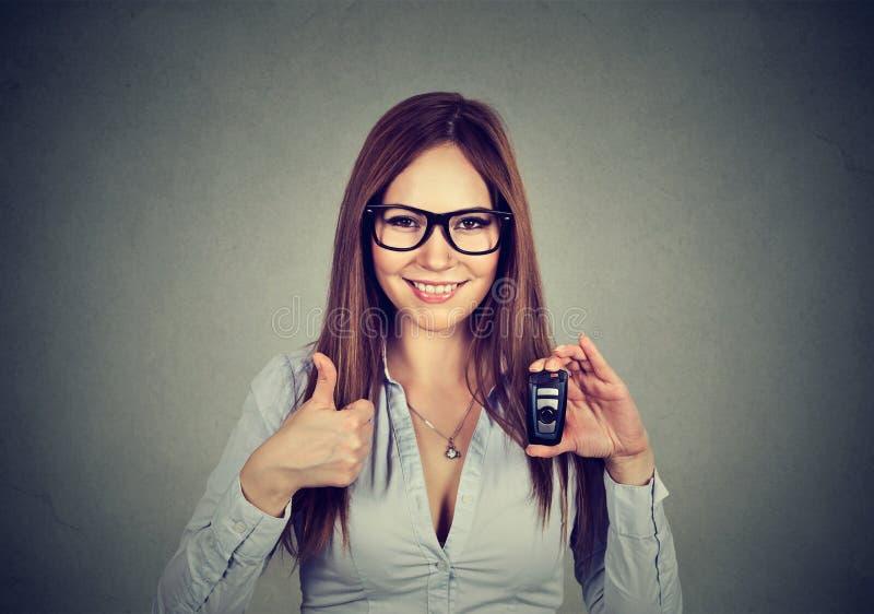 Счастливая женщина показывая удаленные ключи и большие пальцы руки автомобиля вверх стоковые фотографии rf