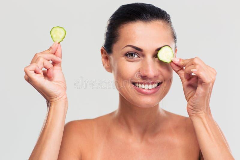 Счастливая женщина покрывая ее глаз с огурцом стоковое фото rf