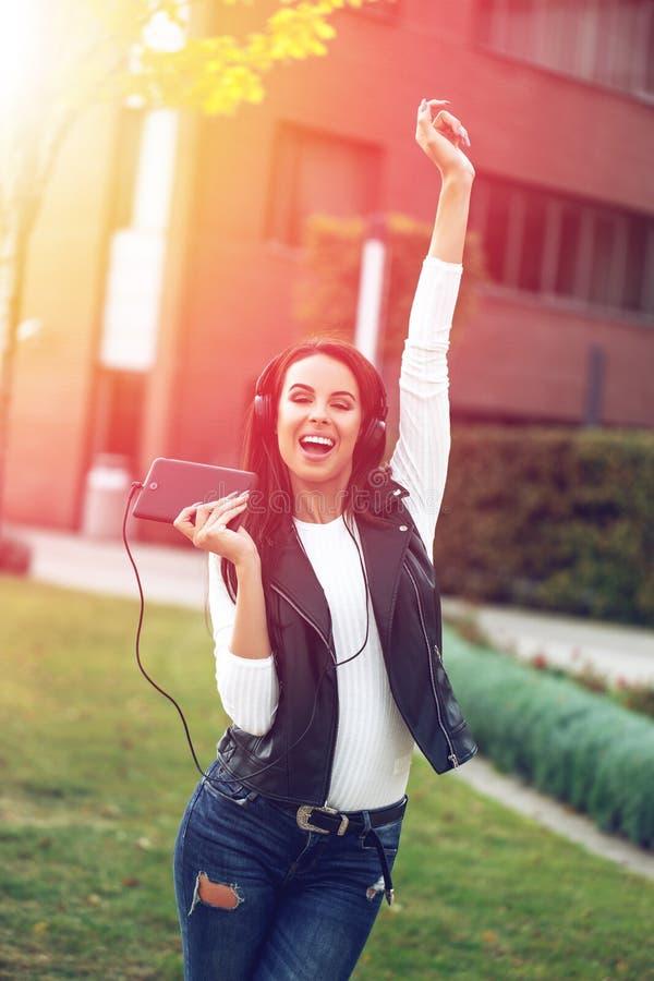 Счастливая женщина поя и танцуя в заходе солнца стоковое изображение