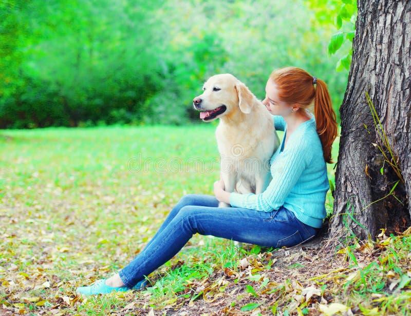 Счастливая женщина предпринимателя и собака золотого Retriever совместно сидят около дерева в парке стоковое фото rf