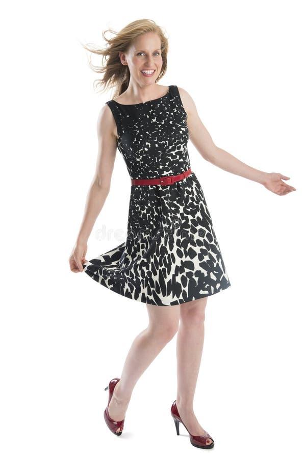 Счастливая женщина представляя в безрукавном платье стоковое фото rf