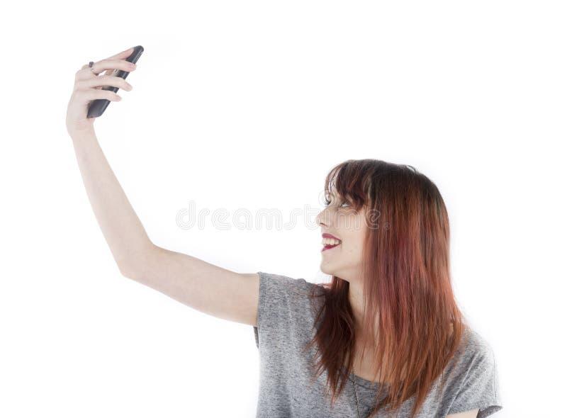 Счастливая женщина принимая Selfie используя телефон стоковое фото rf