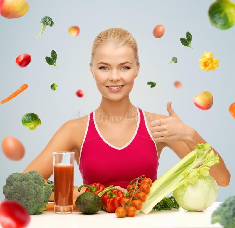 Счастливая женщина при вегетарианская еда показывая большие пальцы руки вверх стоковое изображение