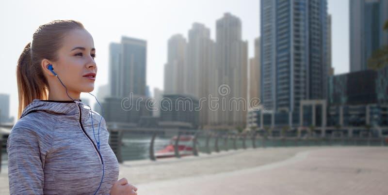 Счастливая женщина при наушники бежать над городом Дубай стоковые фото