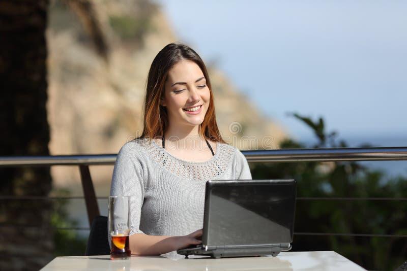 Счастливая женщина работая с ее компьтер-книжкой в террасе гостиницы стоковое изображение