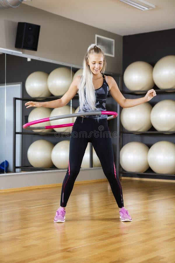 Счастливая женщина работая с обручем Hula в спортзале стоковое фото rf