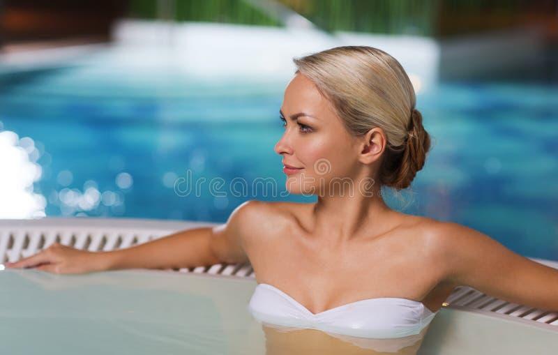 Счастливая женщина сидя в джакузи на poolside стоковое фото