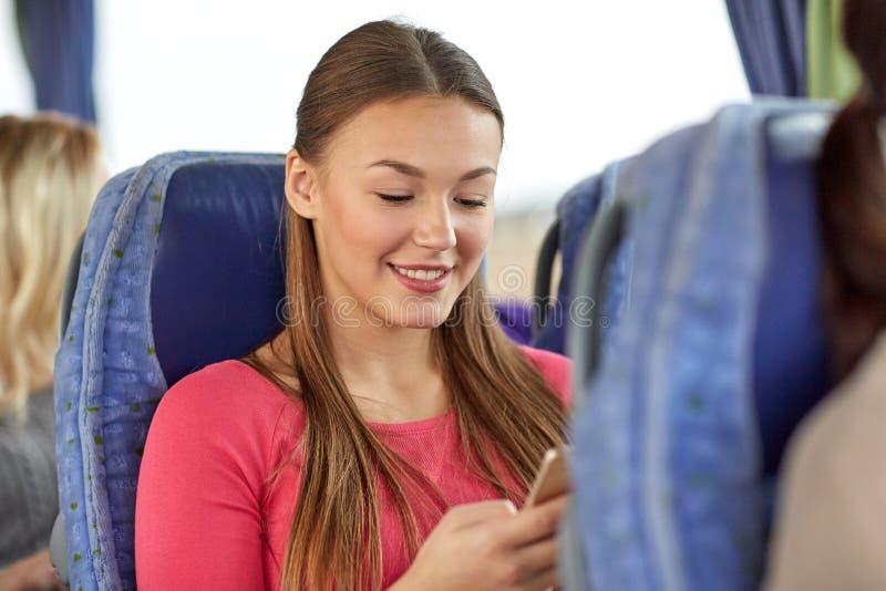 Счастливая женщина сидя в шине перемещения с smartphone стоковые изображения