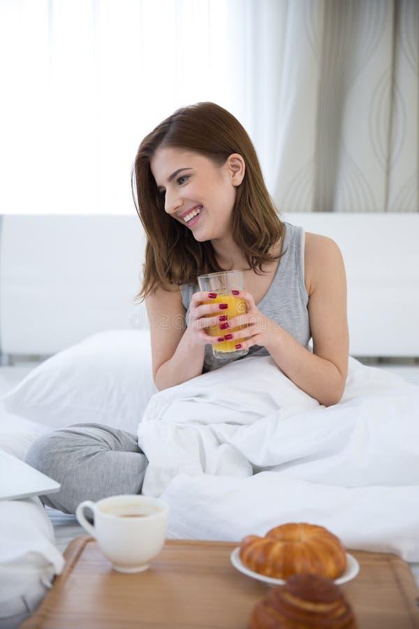 Счастливая женщина сидя на кровати с апельсиновым соком стоковое изображение rf