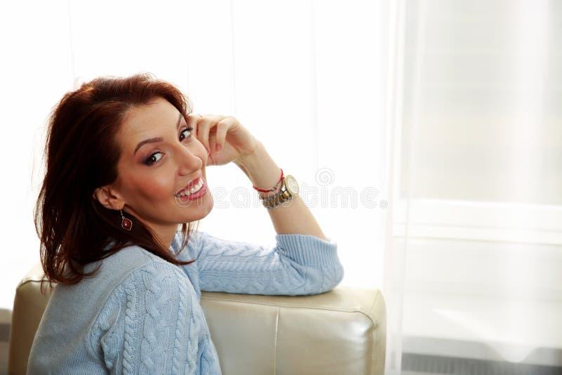 Download Счастливая женщина сидя на софе Стоковое Изображение - изображение насчитывающей привлекательностей, indoors: 37926897
