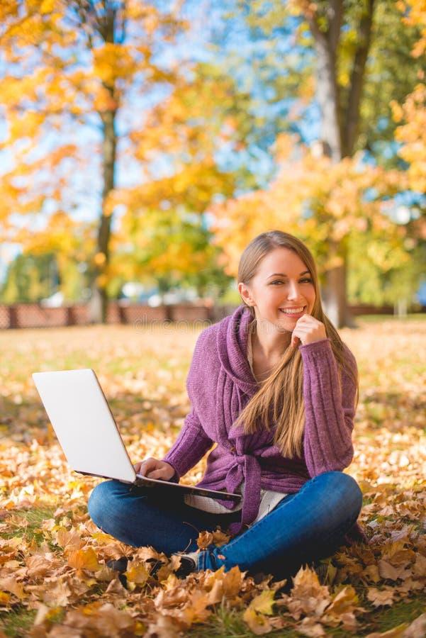 Счастливая женщина сидя на травянистой земле используя компьтер-книжку стоковые фото