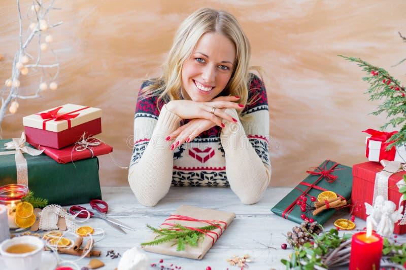 Счастливая женщина сидя таблицей и подготавливая подарки стоковая фотография