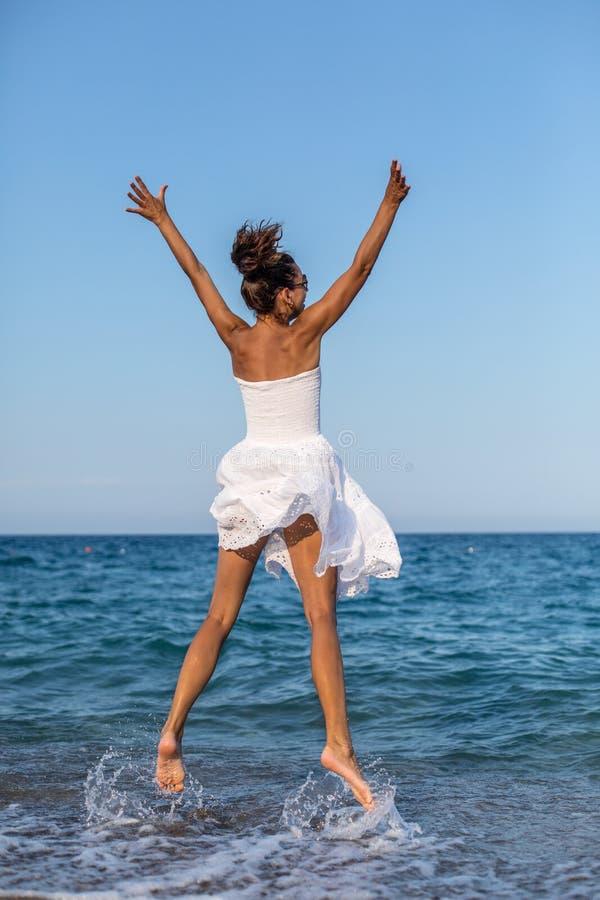 Счастливая женщина скача на взморье стоковые изображения rf