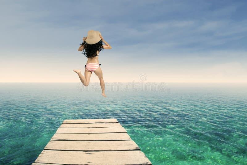 Счастливая женщина скача на пристань 1 стоковая фотография rf