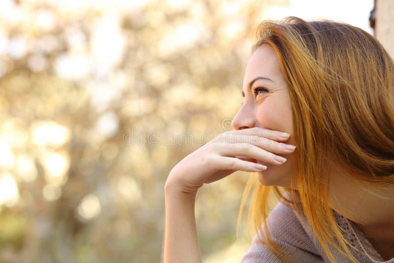 Счастливая женщина смеясь над покрывающ ее рот стоковое фото