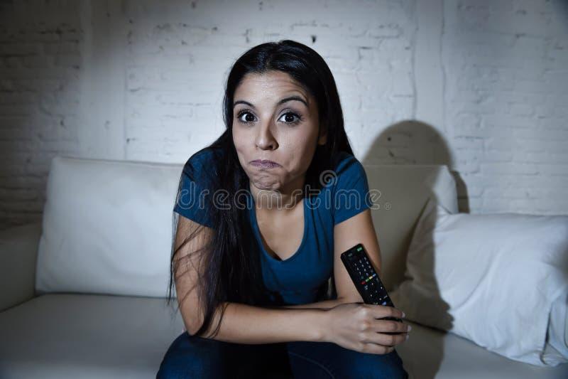 Счастливая женщина смотря телевидение на возбужденном кресле софы наслаждающся романтичным фильмом или выставкой стоковое фото rf