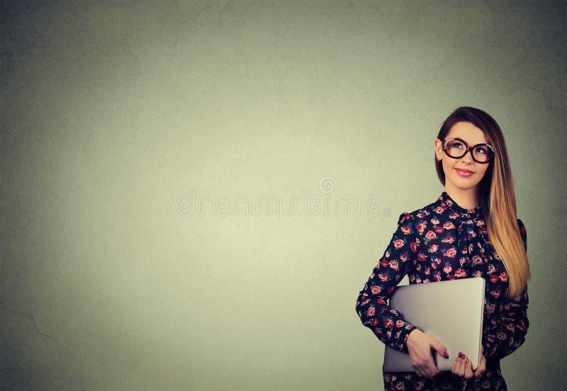 Счастливая женщина стоя с компьтер-книжкой над серой предпосылкой стены стоковое фото rf