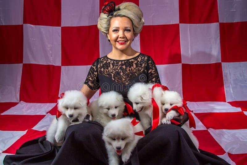 Счастливая женщина с белыми щенятами стоковые фото