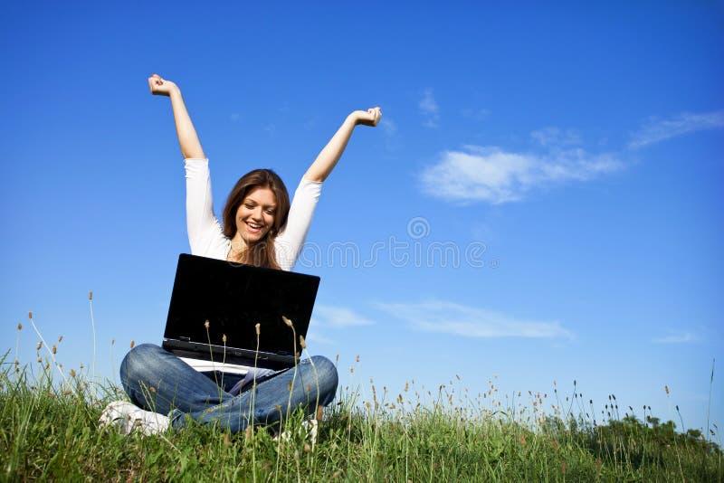 Счастливая женщина с компьтер-книжкой стоковое фото