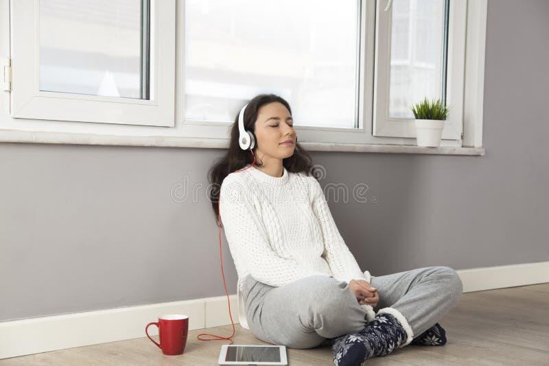 Счастливая женщина слушая к музыке дома стоковая фотография