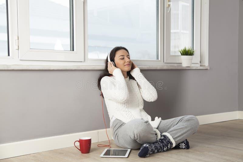 Счастливая женщина слушая к музыке дома стоковые изображения rf