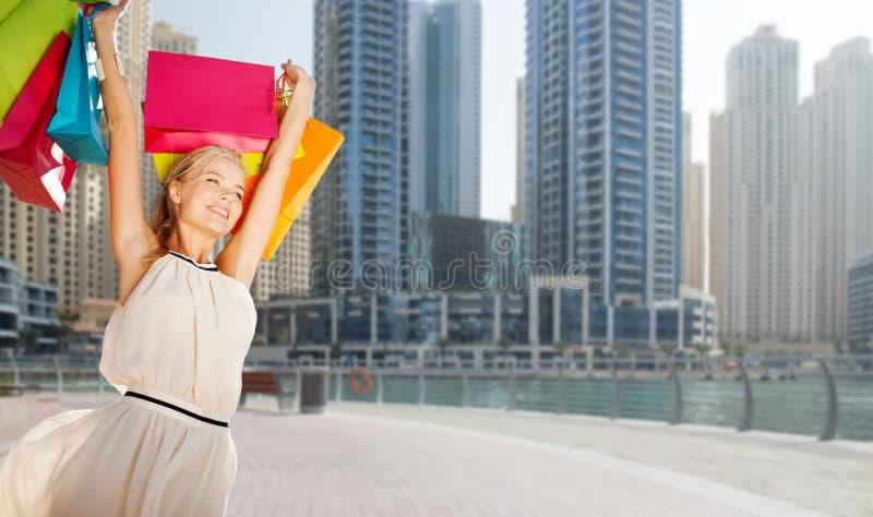 Счастливая женщина с хозяйственными сумками над городом Дубай стоковые изображения