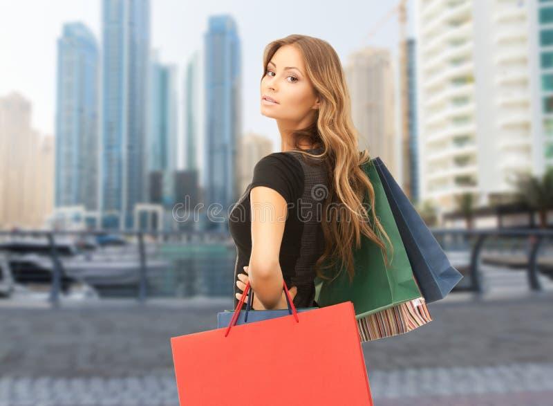 Счастливая женщина с хозяйственными сумками над городом Дубай стоковая фотография rf