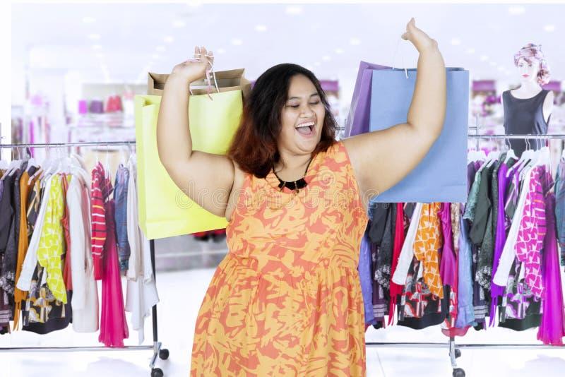 Счастливая женщина с хозяйственными сумками на моле стоковое фото rf