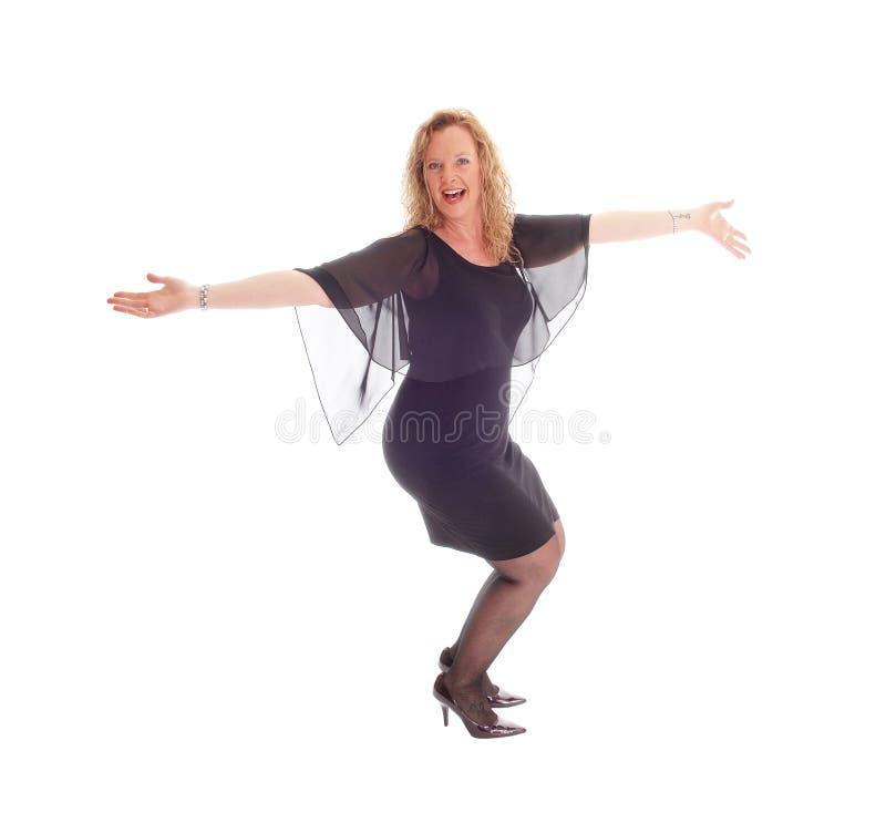 Счастливая женщина танцев в черном платье стоковые изображения rf