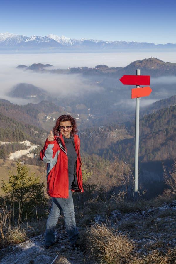 Счастливая женщина hiker на знаке о'кей показа горы верхнем стоковое изображение rf