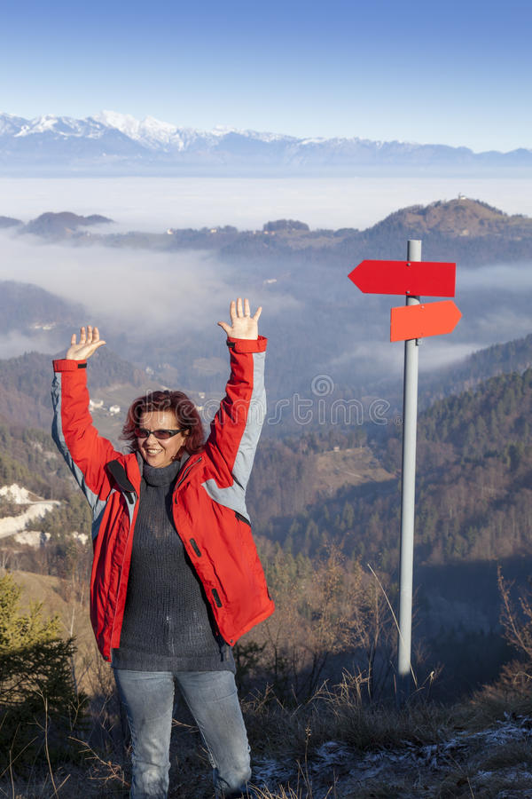 Счастливая женщина hiker на здравствуйте! горы верхнем развевая стоковое фото