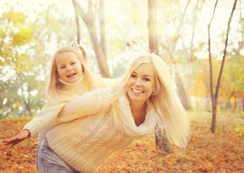 Счастливая жизнерадостная мать держа усмехаясь ребёнок и игру совместно в солнечном парке осени стоковое изображение