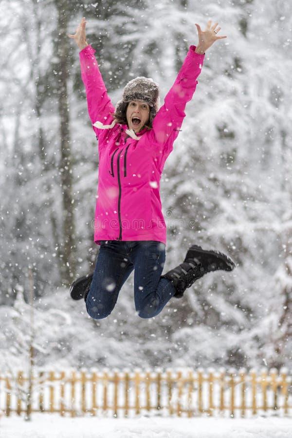Счастливая жизнерадостная молодая женщина скача высоко вверх в воздух поднимаясь он стоковые фотографии rf