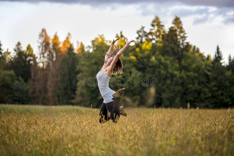 Счастливая жизнерадостная молодая женщина скача в воздух в середине g стоковые изображения rf