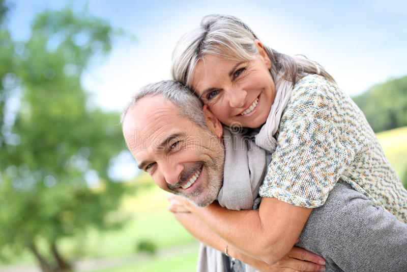 Счастливая задняя часть нося жены старшего человека дальше стоковые фотографии rf