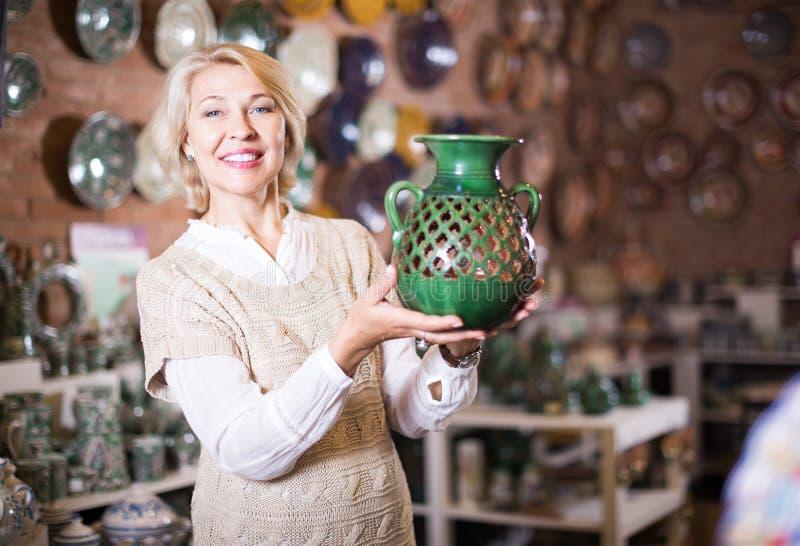 Счастливая зрелая женщина представляя с керамическим cookware стоковые изображения