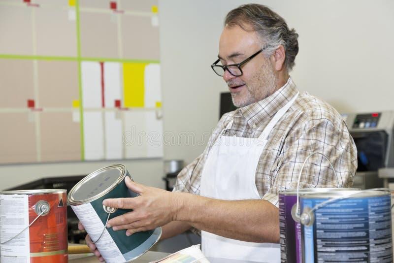 Счастливая зрелая краска инструкций чтения клерка продаж может в магазине оборудования стоковое изображение