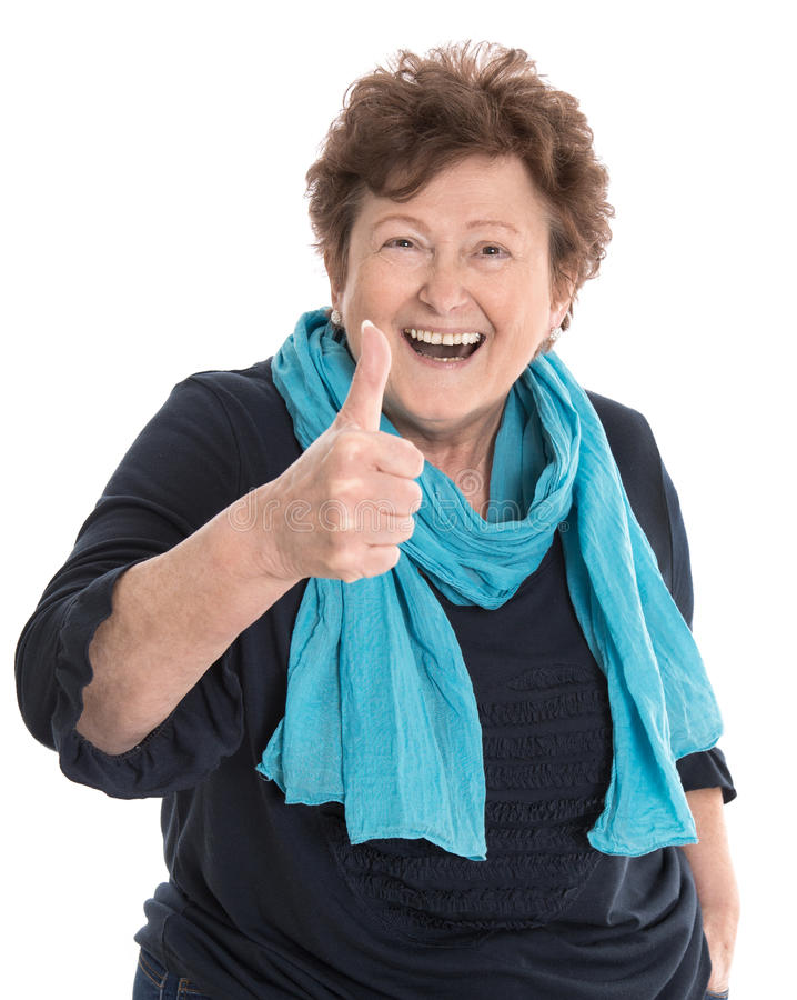 Счастливая изолированная более старая дама нося голубые одежды с большим пальцем руки вверх по ges стоковые изображения rf