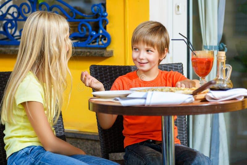 Счастливая или удовлетворенная девушка ширины мальчика есть пиццу и стоковое изображение