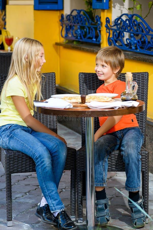 Счастливая или удовлетворенная девушка ширины мальчика есть пиццу и стоковые фото