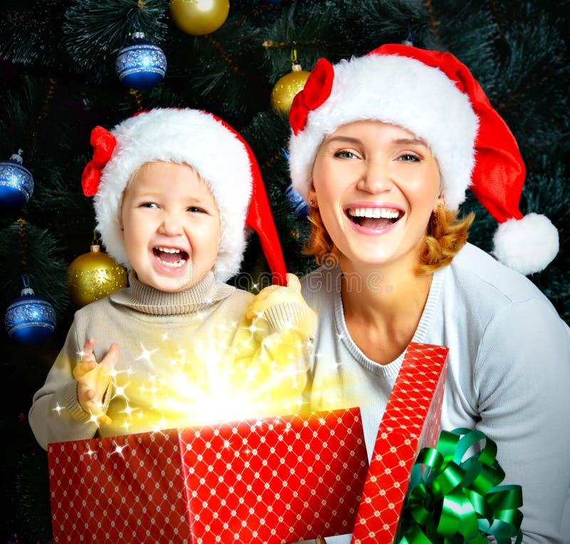 Счастливая и смеясь над мать с маленьким ребенком держит коробку с gi стоковая фотография rf