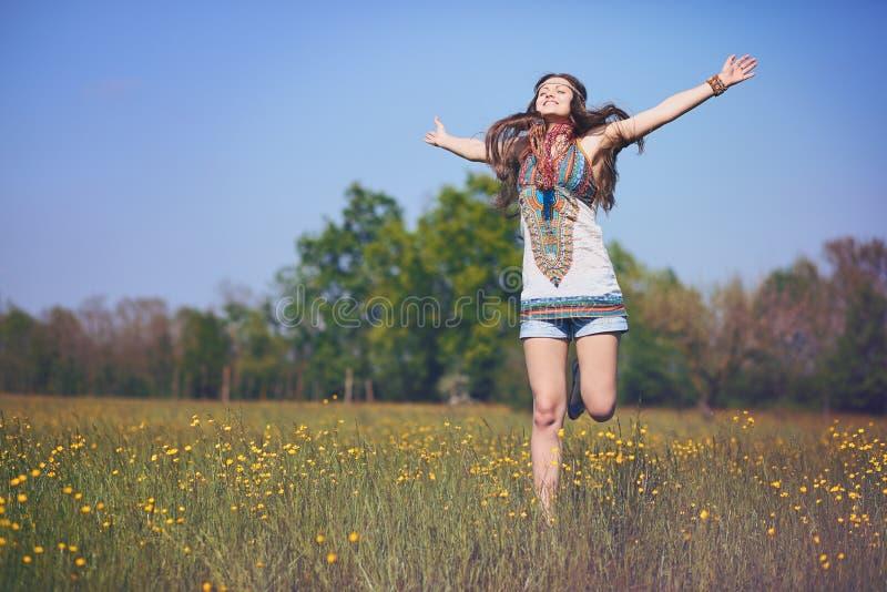 Счастливая и усмехаясь женщина hippie скачет стоковое фото rf
