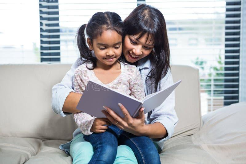 Счастливая книга чтения матери с ее дочерью стоковые фото