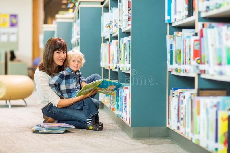 Счастливая книга чтения мальчика и учителя в библиотеке стоковые изображения rf